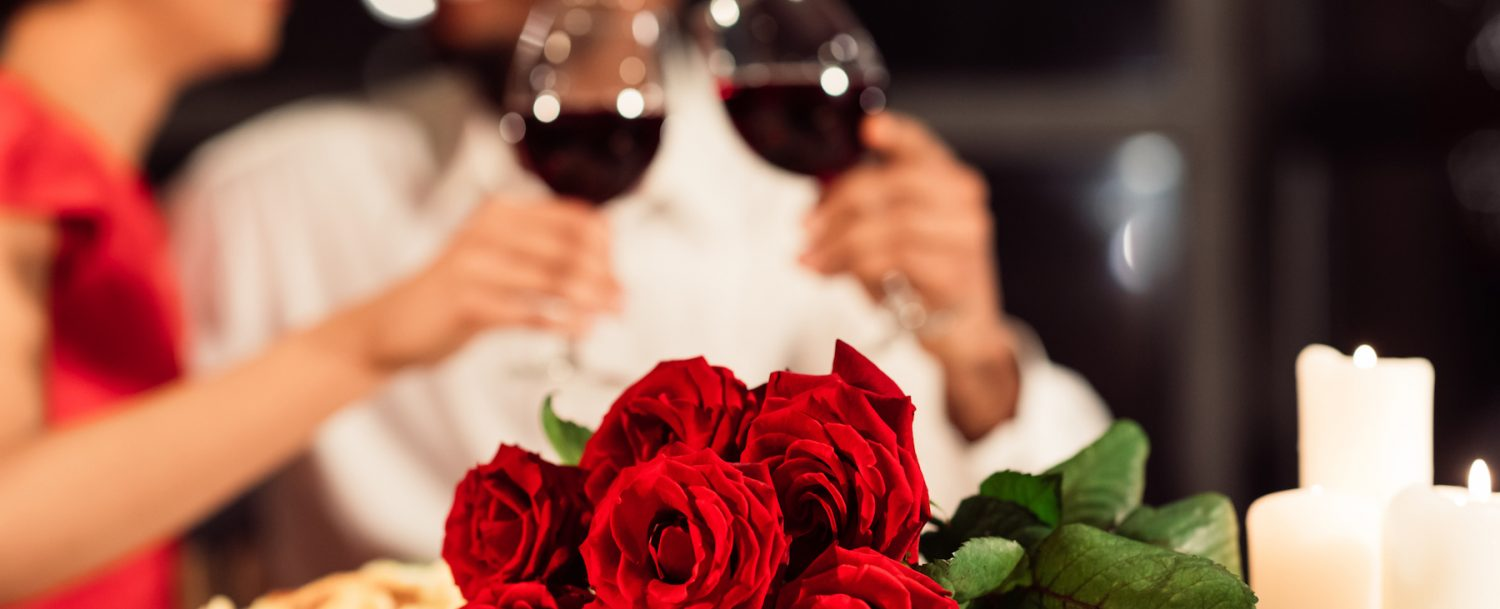 Valentine's Romantic Date. Red Roses Lying On Table, Unrecognizable Spouses Drinking Wine In Restaurant. Selective Focus, Cropped (Valentine's Romantic Date. Red Roses Lying On Table, Unrecognizable Spouses Drinking Wine In Restaurant. Selective Focus