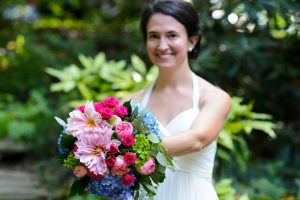 a blushing bride holding her bouquet after the wedding